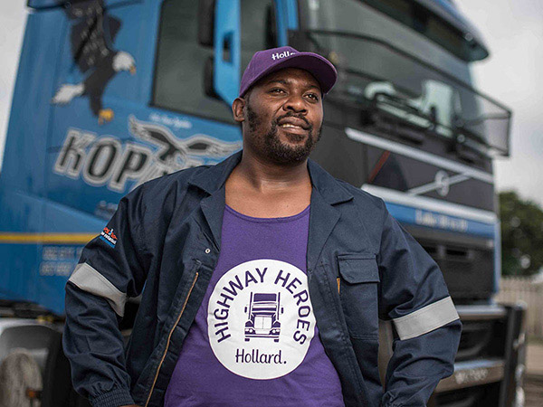 A Highway Heroes Driver wearing HH-branded t-shirt and cap standing proudly in front of his truck.
